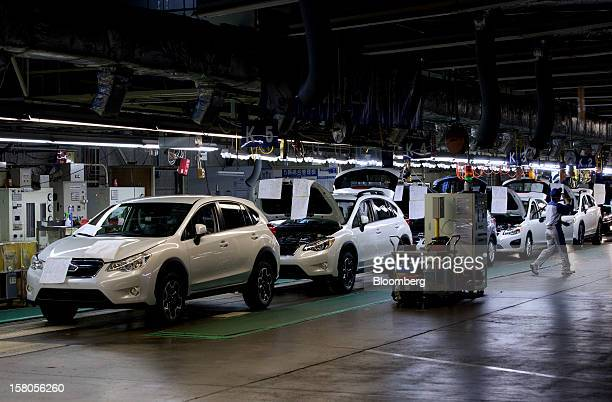 A worker walks past Fuji Heavy Industries Ltd Subaru branded vehicles in the inspection area of the company's Gunma Yajima Plant in Ota City Gunma...