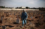 A worker walks past graves as they construct a layered cemetery in the rebelheld town of Douma east of the Syrian capital Damascus on November 9 2015...