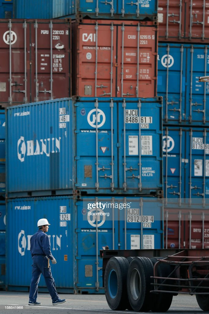 A worker walks past Hanjin Shipping Co. containers stacked at a container terminal in Tokyo, Japan, on Tuesday, Dec. 18, 2012. Japan's exports fell for a sixth month in November and the trade deficit swelled, underscoring the challenge that incoming Prime Minister Shinzo Abe faces in reviving growth. Photographer: Kiyoshi Ota/Bloomberg via Getty Images