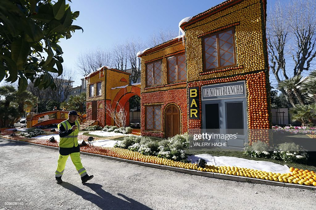 A worker walks past house sculptures decorated with oranges and lemons in Menton on the French Riviera on February 11, 2016, ahead of the start of the 'Fete du Citron' (Lemon Festival). The theme of this 83rd edition, running from February 13 until March 2, 2016, is called 'Cinecitta'. / AFP / VALERY HACHE