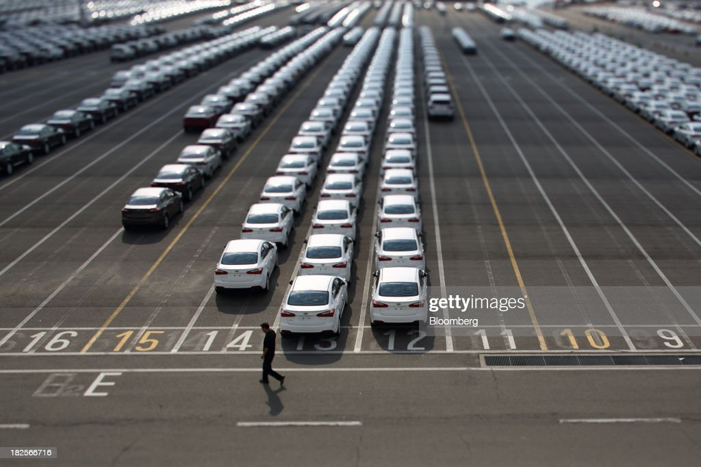A worker walks past Kia Motors Corp. vehicles bound for export in this photograph taken with a tilt-shift lens at the port of Pyeongtaek in Pyeongtaek, South Korea, on Monday, Sept. 30, 2013. South Koreas consumer confidence sank to a five-month low in September, even after a rebound in exports fueled the fastest economic growth in two years last quarter. Photographer: SeongJoon Cho/Bloomberg via Getty Images