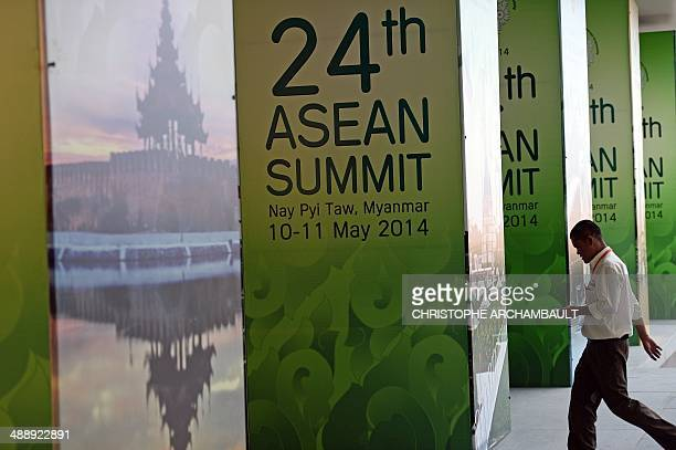 A worker walks past postercovered pillars outside the venue of the upcoming ASEAN Summit at the Myanmar International Convention Center in the...