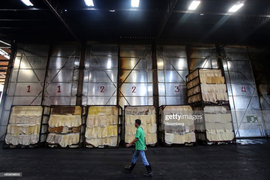 A worker walks past racks of rubber sheets drying at the Thai Hua Rubber Pcl factory in Samnuktong, Rayong province, Thailand, on Wednesday, Jan. 29, 2014. Rubber production in Thailand, the world's largest exporter, may decline as growers from the main producing regions join protests seeking to overthrow the government, according to Von Bundit Co. Photographer: Dario Pignatelli/Bloomberg via Getty Images