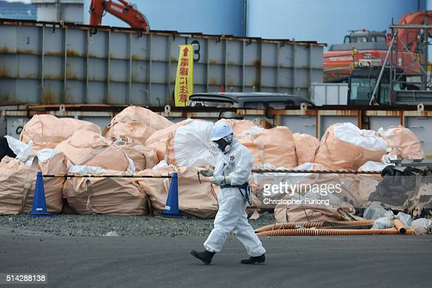 A worker walks past radioactive waste as the decontamination process continues at the Tokyo Electric Power Co's embattled Fukushima Daiichi nuclear...