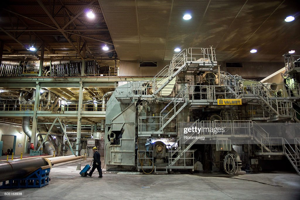 A worker walks past the front end of the paper machine where the pulp enters before being processed into newsprint paper at the Resolute Forest...