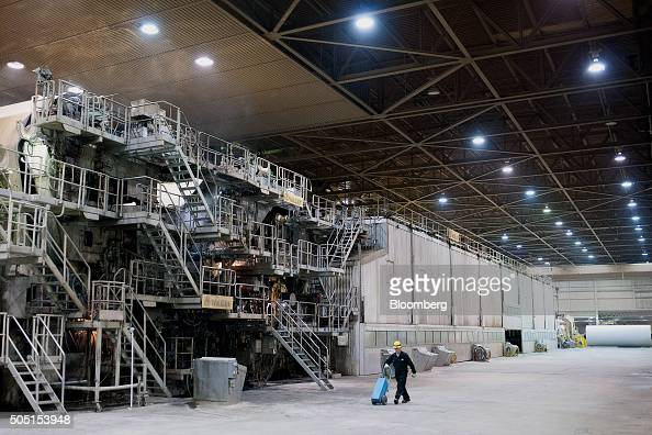 A worker walks past the giant pulp and paper machine at the Resolute Forest Products mill in Thunder Bay Canada Ontario on Thursday Jan 7 2016...