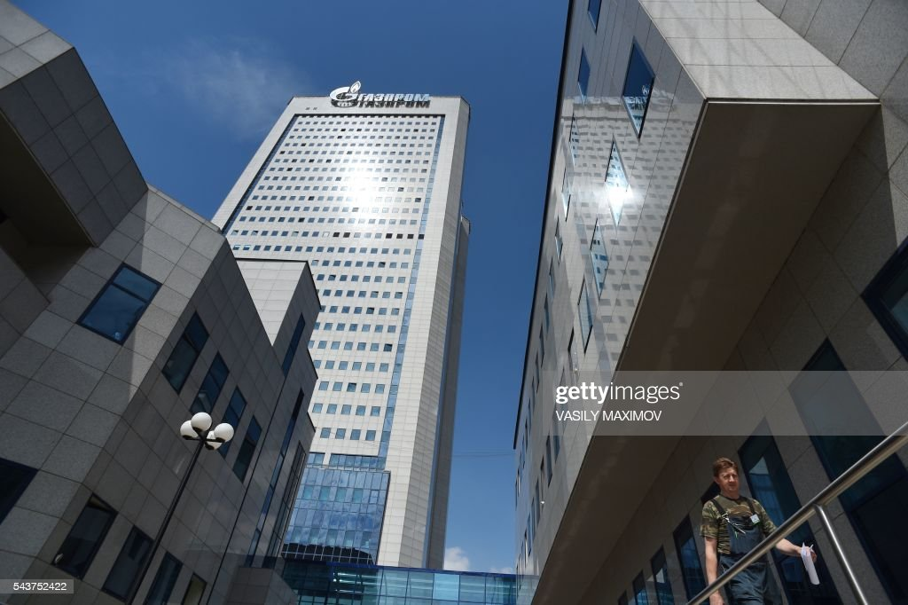 A worker walks past the headquarters of Gazprom during the annual meeting of the company's shareholders in Moscow on June 30, 2016. / AFP / VASILY