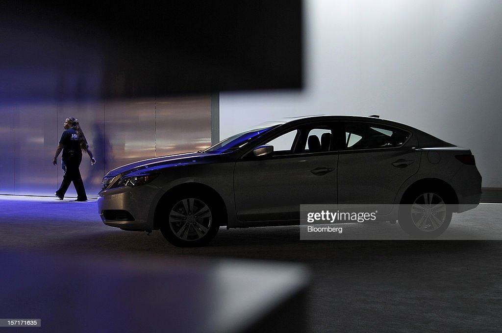 A worker walks past the Honda Motor Co. Acura ILX vehicle displayed at the company's booth during the LA Auto Show in Los Angeles, California, U.S., on Thursday, November 29, 2012. In the quickest turnaround in the 39-year history of the Civic, Honda Motor Co. introduced a modified U.S. model, just 19 months after the current car appeared. Photographer: Jonathan Alcorn/Bloomberg via Getty Images