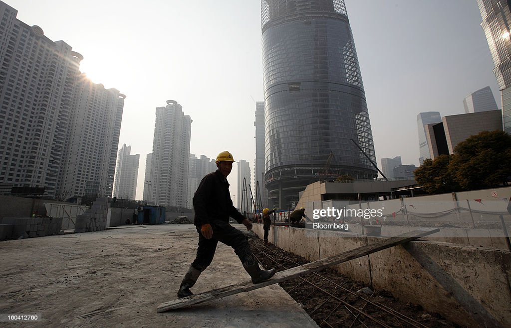 A worker walks through a construction site for a commercial building in the Pudong area of Shanghai, China, on Wednesday, Jan. 30, 2013. China's economic growth accelerated for the first time in two years as government efforts to revive demand drove a rebound in industrial output, retail sales and the housing market. Photographer: Tomohiro Ohsumi/Bloomberg via Getty Images