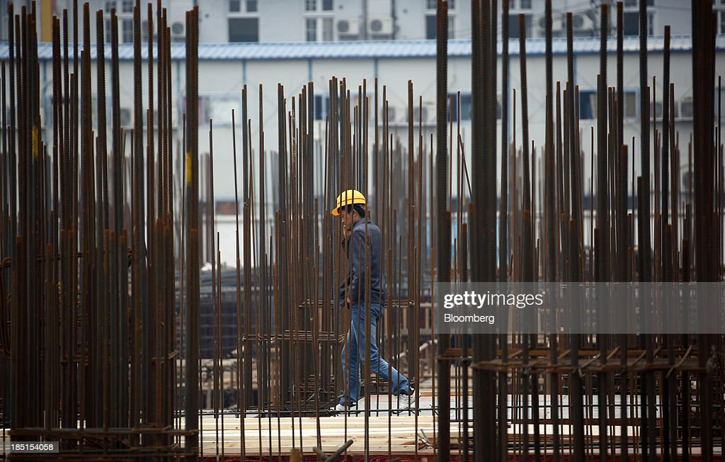 A worker walks through a construction site for a residential property in Wuhan, China, on Thursday, Oct. 17, 2013. China is scheduled to release third-quarter gross domestic product figures on Oct. 18. Photographer: Tomohiro Ohsumi/Bloomberg via Getty Images