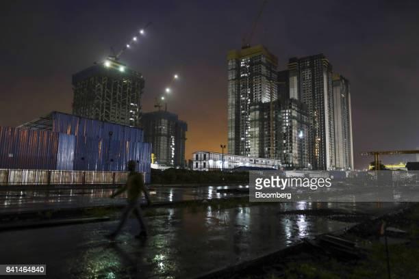 A worker walks through the Mumbai Metro Rail Corp casting yard as buildings under construction stand illuminated at night in Mumbai India on Monday...