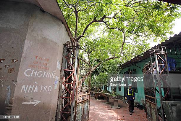 A worker walks through the yard of housing that provides accommodation to workers of the Samsung Electronics Vietnam Co Plant in Ap Don hamlet Bac...