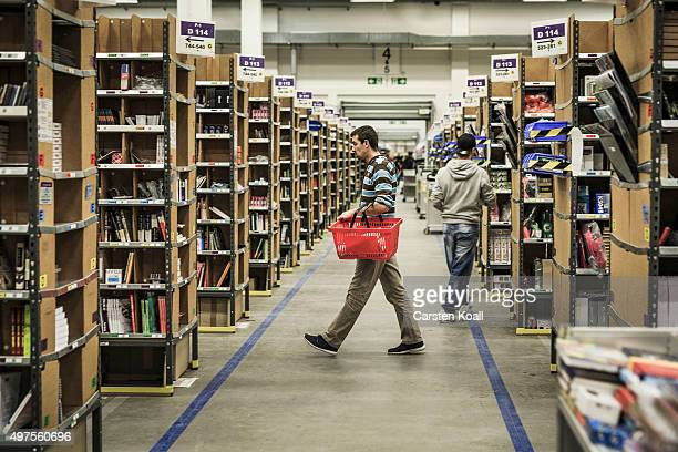 A worker walks to fill inventory among shelves lined with goods at an Amazon warehouse on November 17 2015 in Brieselang Germany Germany is online...