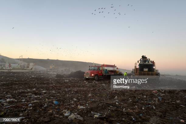 A worker walks towards a bulldozer in a landfill cell at the Melbourne Regional Landfill site operated by Cleanaway Waste Management Ltd in Ravenhall...