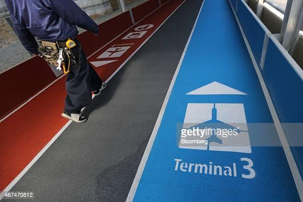 A worker walks towards Terminal 3 of Narita Airport in Narita Japan on Wednesday March 25 2015 The airport operator Narita International Airport Corp...