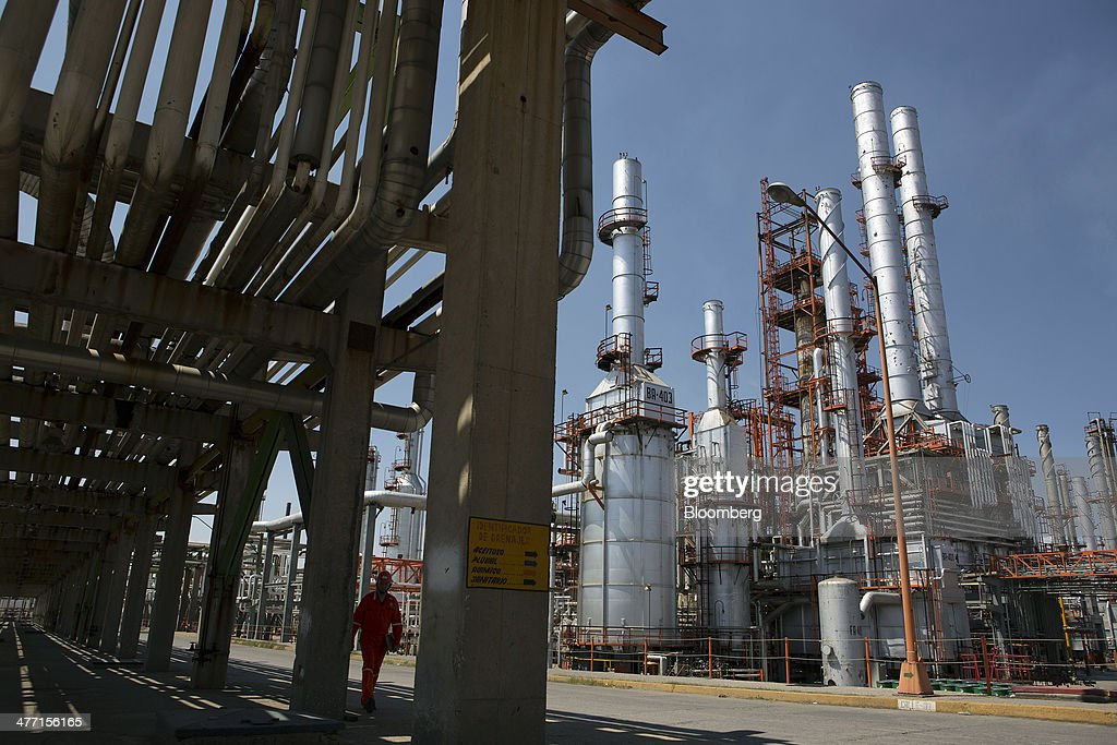 A worker walks underneath a row of pipes at the Petroleos Mexicanos Miguel Hidalgo Refinery in Tula de Allende Mexico on Thursday March 6 2014 The...