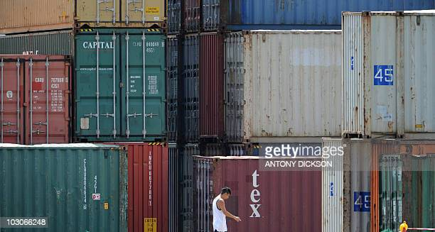 A worker wals past shipping containers along Victoria harbour on July 24 2010 Hong Kong's exports soared 244 percent in May official data showed on...