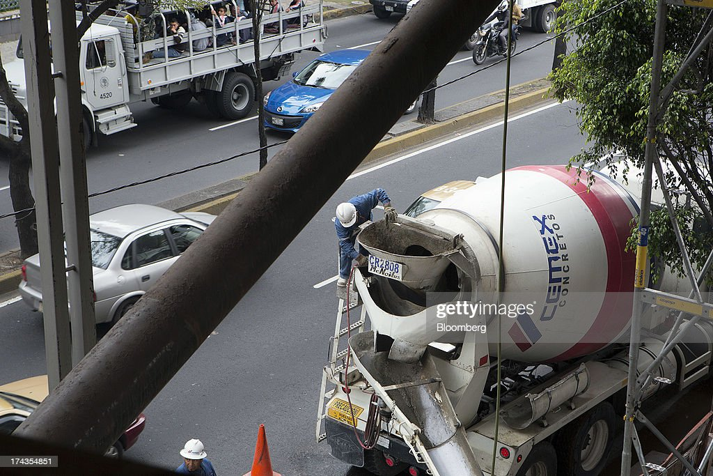 A worker washes a Cemex SAB truck after pouring concrete during construction of a building in Mexico City, Mexico. on Friday, July 19, 2013. Mexican President Enrique Pena Nietos $320 billion infrastructure plan is reviving a rally in cement maker Cemex SABs bonds after the emerging-market rout derailed an advance fueled by the U.S. housing rebound. Photographer: Susana Gonzalez/Bloomberg via Getty Images