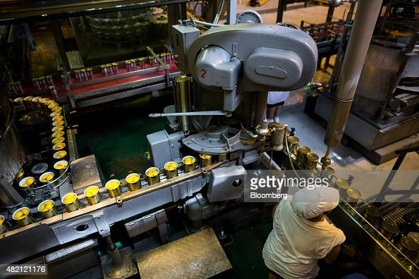 A worker watches a machine as it seals cans of peach halves and syrup on the canning production line at the Agricultural Corporate Collaboration SA...