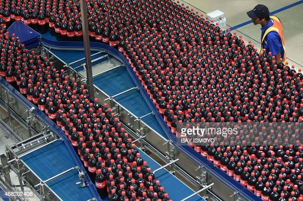 A worker watches a production line of a new CocaCola plant in Cikedokan BekasiWest Java on March 31 2015 The newly inaugurated CocaCola company new...