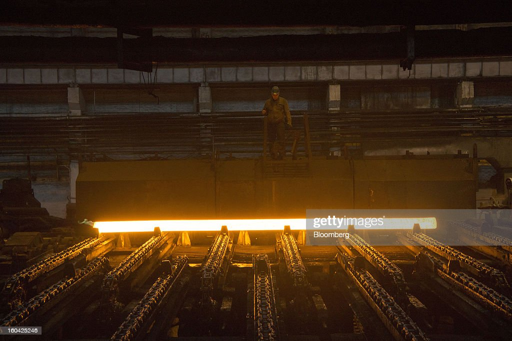A worker watches as a billet of red hot steel rolls along the production line at the Interpipe LLC pipe factory in Dnipropetrovsk, Ukraine, on Wednesday, Jan. 30, 2013. Ukraine's Interpipe Group, owned by billionaire Victor Pinchuk, opened a $700 million electric steel mill in Dnipropetrovsk with an annual output capacity of 1.32 million tons of steel for its seamless pipe production. Photographer: Vincent Mundy/Bloomberg via Getty Images