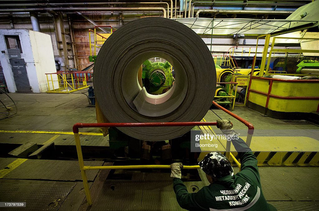 A worker watches as a drum of steel sheeting moves along the production line at OAO Mechel's metallurgical plant in Chelyabinsk, Russia, on Wednesday, July 17, 2013. Mechel, the country's largest producer of coking coal for steelmakers has begun operating its $700m rail production line which can produce 100 meter rails. Photographer: Andrey Rudakov/Bloomberg via Getty Images