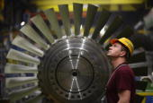 A worker watches as a heavy piece for a turbine moves above him while standing in front of a rotor assembly at the Siemens gas turbine factory on...