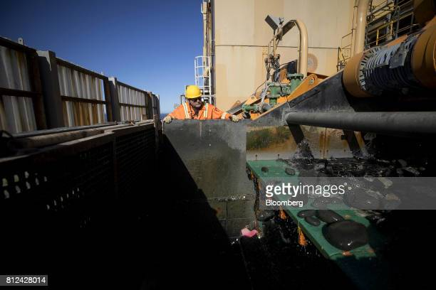 A worker watches as a high pressure spray cleans discarded rock from the seabed following processing before returning to the sea aboard the Mafuta...