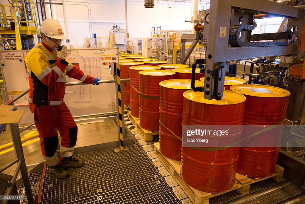 A worker watches as a machine caps oil drums containing lubricant oil at the Royal Dutch Shell Plc lubricants blending plant in Torzhok Russia on...