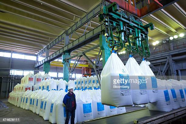 A worker watches as bags of fertilizer are moved by a mechanical hoist and loaded onto a conveyor belt at the OAO Phosagro plant in Cherepovets...