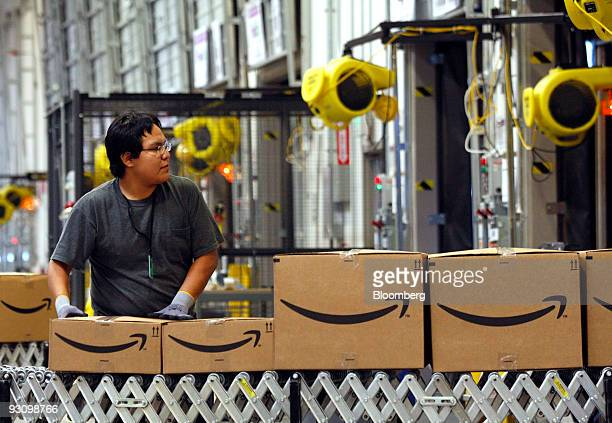A worker watches as boxed merchandise moves along a conveyor belt to a waiting truck for delivery at the Amazoncom Phoenix Fulfillment Center in...