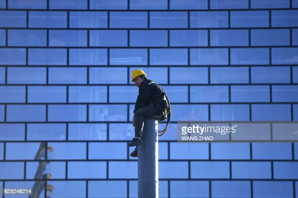 A worker watches as he sits on a pillar at a construction site in Beijing on November 232016 Chinese exports sank for a seventh consecutive month in...