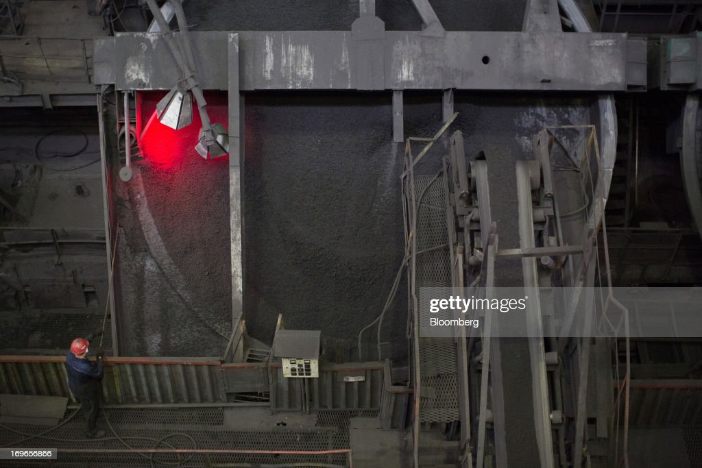 A worker watches as iron ore pellets pass through a machine at the Lebedinsky GOK (LGOK) iron ore mining and processing plant, operated by Metalloinvest Holding Co., in Gubkin, Russia, on Tuesday, May 28, 2013. Lebedinsky, Russia's third biggest iron ore mine, is owned 81 percent owned by Russian billionaire Alisher Usmanov, who also owns Mikhailovsky GOK, Russia's second-biggest iron ore mine, and Oskol Electrometallurgical Combine, a steel plant supplied by Lebedinsky. Photographer: Andrey Rudakov/Bloomberg via Getty Images