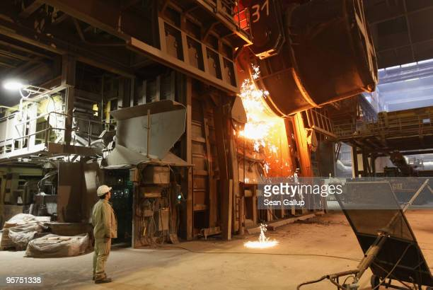 A worker watches as molten iron flows into a furnace for purification and alloying to become steel at the ThyssenKrupp steelworks on January 13 2010...