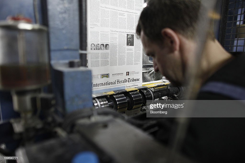 A worker watches as pages of the International Herald Tribune newpaper run through the print presses at the Kathimerini printing plant in Paiania, Greece, on Thursday, Jan. 17, 2013. An anarchist group claimed responsibility for a series of attacks early on Jan. 11 when unidentified perpetrators threw makeshift bombs made from propane gas canisters into the homes of five Greek journalists working for national media saying it was to protest coverage of the country's financial crisis seen as sympathetic to the government. Photographer: Kostas Tsironis/Bloomberg via Getty Images