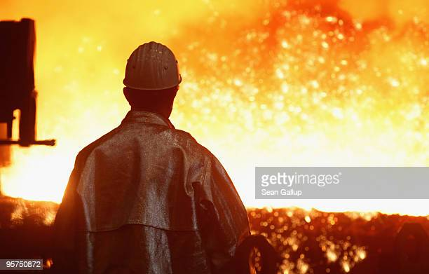 A worker watches as sparks fly from molten iron heated to approximately 1480 degrees Celsius flowing from a blast furnace at the ThyssenKrupp...