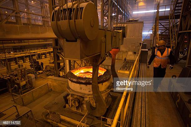 A worker watches from a platform as a ladle carries molten steel between processing facilities at the metallurgical mill operated by OAO Novolipetsk...