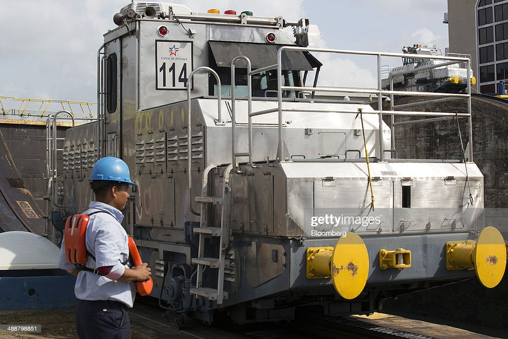 A worker watches over an electronic locomotive, known as a mule, as it guides a vessel through the Miraflores Locks at the Panama Canal near Panama City, Panama, on Wednesday, April, 23, 2014. Construction projects throughout Panama have remained idle since April 23, when workers walked off the job in an effort to win a 35 percent salary increase. The strike threatens to further delay the canals expansion, designed to accommodate larger ships and help reduce transport costs for commodities such as liquefied natural gas. Photographer: Susana Gonzalez/Bloomberg via Getty Images