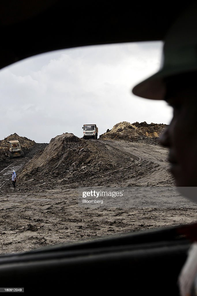A worker watches trucks and excavators operating at the PT Exploitasi Energi Indonesia open pit coal mine in Palaran, East Kalimantan province, Indonesia, on Friday, Sept. 13, 2013. Prices of power-station coal in Indonesia, the worlds biggest exporter, may be little changed in coming weeks, according to Bloomberg News survey. Photographer: Dadang Tri/Bloomberg via Getty Images