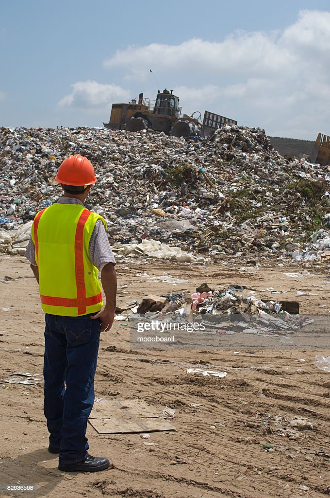 Worker watching digger moving waste at landfill site : Stock Photo