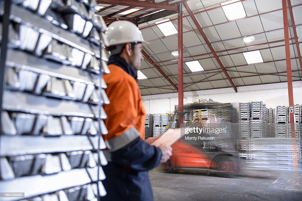 Worker watching forklift truck carrying alumninium ingots in warehouse, blurred motion