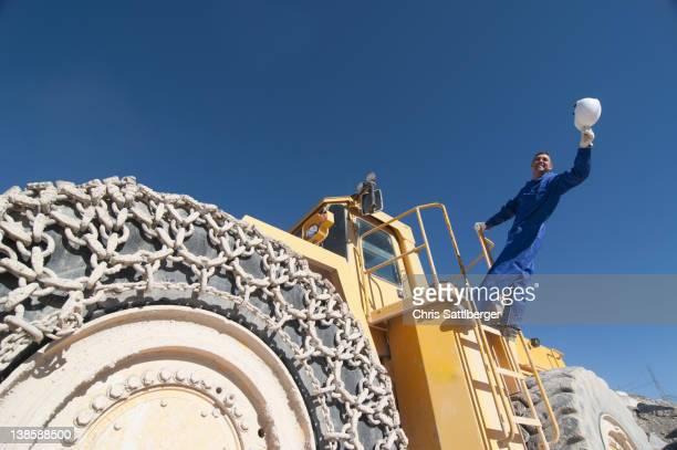 worker waving hard hat standing on mining machine