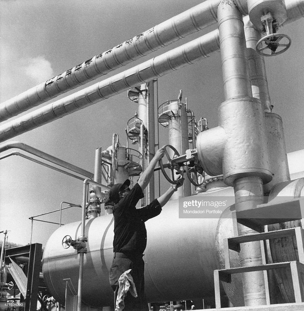 'A worker wearing a cap and sunglasses regulates the pressure within a pipeline rotating a valve in the zone of Bassora rich of oil field and...