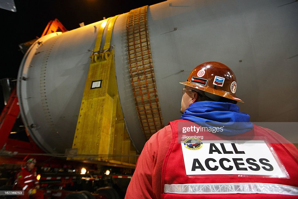 A worker wearing a hard hat monitors the transport of a steel coke drum as it travels along the Pacific Coast Highway on a trailer manufactured by Mammoet Salvage BV between Redondo Beach and El Segundo, California, U.S., on Wednesday, Feb. 20, 2013. The drum, which measures over 100 feet long and weighs more than 500,000 pounds is one of six scheduled to be delivered to Chevron Corp.'s refinery in El Segundo. Photographer: Patrick Fallon/Bloomberg via Getty Images