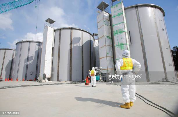 A worker wearing a protective suit and a mask looks up welding storage tanks for radioactive water under construction in the J1 area at the Tokyo...