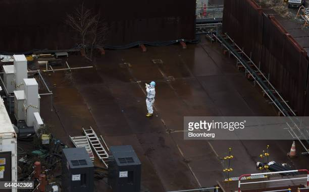 A worker wearing a protective suit and a mask takes a photograph at Tokyo Electric Power Co's Fukushima Daiichi nuclear power plant in Okuma...