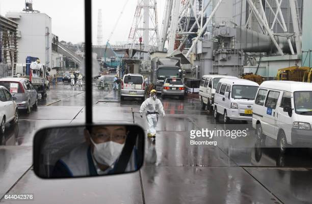 A worker wearing a protective suit and a mask walks through Tokyo Electric Power Co's Fukushima Daiichi nuclear power plant in Okuma Fukushima Japan...