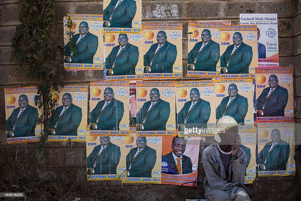 A worker wearing a safety helmet sits on a roadside in front of political election posters for Elias Otieno Okumu in Nairobi, Kenya, on Friday, March 1, 2013. Next week's presidential vote will be the first since disputed elections in 2007 triggered ethnic fighting in which more than 1,100 people died and another 350,000 fled their homes. Photographer: Trevor Snapp/Bloomberg via Getty Images