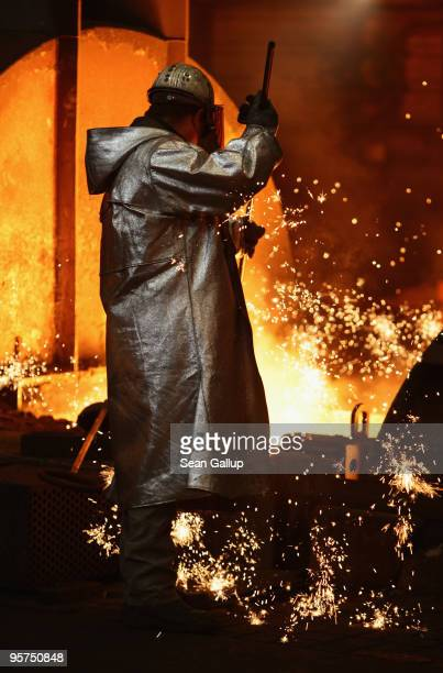 A worker wearing protective clothing takes a sample of molten iron heated to approximately 1480 degrees Celsius flowing from a blast furnace at the...