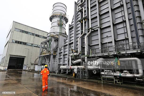 A worker wearing Royal Dutch Shell Plc branded overalls walks through the grounds of the Afam VI energy generation plant operated by the Shell...